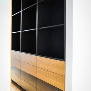 Imagen de armario vestidor unisex, actual, grande, con puertas de armario negras, suelo de madera clara y suelo amarillo