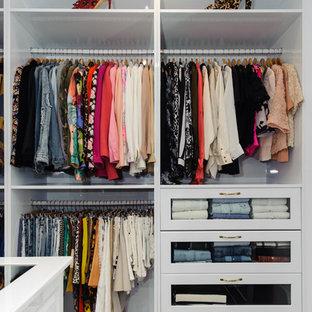 Ejemplo de armario vestidor de mujer, moderno, extra grande, con suelo de madera oscura, armarios abiertos, puertas de armario blancas y suelo marrón