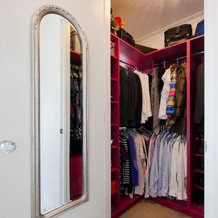 Exemple d'un dressing tendance neutre et de taille moyenne avec un placard à porte plane, des portes de placard rouges, moquette et un sol beige.