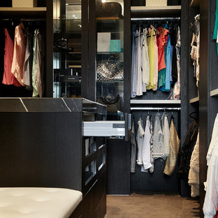 This is an example of a mid-sized contemporary gender-neutral dressing room in Melbourne with black cabinets and carpet.