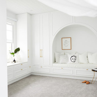 Example of a large beach style gender-neutral carpeted and gray floor walk-in closet design in Sydney with white cabinets and recessed-panel cabinets