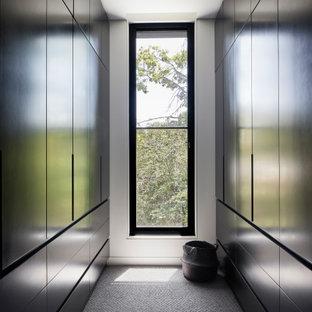 Diseño de armario vestidor unisex, contemporáneo, de tamaño medio, con armarios con paneles lisos, puertas de armario negras, moqueta y suelo gris