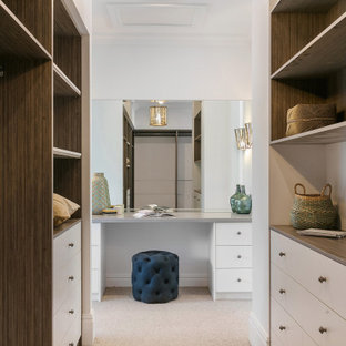 This is an example of a large beach style gender-neutral walk-in wardrobe in Sydney with open cabinets, medium wood cabinets, carpet and beige floor.