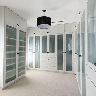 Modelo de armario y vestidor tradicional renovado con armarios tipo vitrina, puertas de armario blancas y moqueta