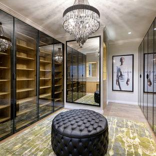 Idee per una grande cabina armadio per donna minimal con ante di vetro, ante in legno chiaro, pavimento in legno massello medio e pavimento marrone