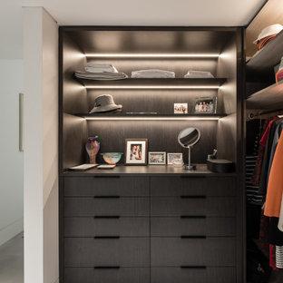 Idées déco pour un dressing room contemporain neutre avec des portes de placard marrons, un sol en carrelage de céramique et un sol beige.