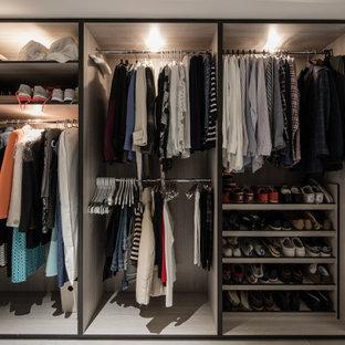 Cette image montre un dressing room design neutre avec des portes de placard marrons, un sol en carrelage de céramique et un sol beige.