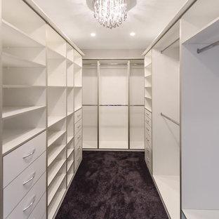 Idées déco pour un très grand dressing moderne pour une femme avec un placard sans porte, des portes de placard blanches et moquette.