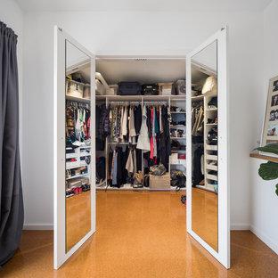 Imagen de armario vestidor unisex, actual, de tamaño medio, con puertas de armario blancas, suelo de corcho y suelo marrón