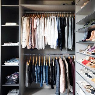 Imagen de armario vestidor de mujer, actual, grande, con armarios abiertos, puertas de armario grises, moqueta y suelo azul
