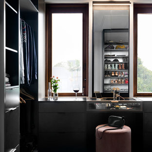 Inspiration for a traditional gender-neutral dressing room in Melbourne with flat-panel cabinets, black cabinets, carpet and blue floor.