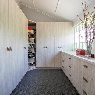 Imagen de armario vestidor bohemio, de tamaño medio, con armarios con paneles lisos, puertas de armario de madera clara, moqueta y suelo gris