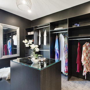Photo of a contemporary gender-neutral walk-in wardrobe in Brisbane with flat-panel cabinets, dark wood cabinets, carpet and grey floor.