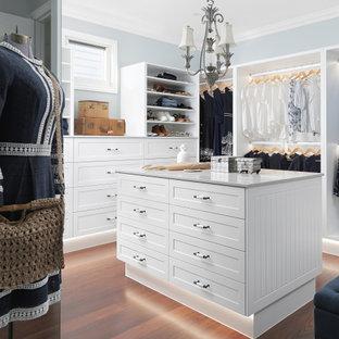 Idéer för mycket stora maritima walk-in-closets för könsneutrala, med skåp i shakerstil, vita skåp, mörkt trägolv och brunt golv