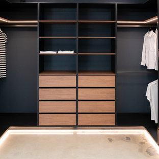 Imagen de armario vestidor actual, de tamaño medio, con armarios abiertos, puertas de armario de madera oscura y suelo de cemento