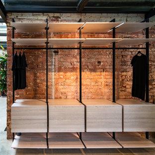 Ejemplo de armario vestidor industrial con armarios abiertos y puertas de armario de madera clara