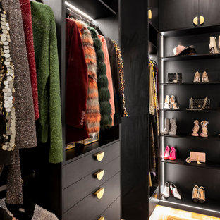 Design ideas for a small contemporary gender-neutral walk-in wardrobe in Brisbane with flat-panel cabinets, dark wood cabinets and light hardwood floors.