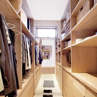 Esempio di una piccola cabina armadio unisex minimalista con ante in legno chiaro, pavimento in travertino e ante lisce