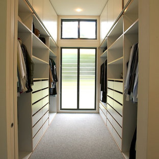 This is an example of a mid-sized contemporary gender-neutral walk-in wardrobe in Gold Coast - Tweed with white cabinets, carpet and flat-panel cabinets.