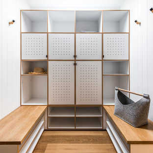 Photo of a contemporary gender-neutral dressing room in Melbourne with flat-panel cabinets, white cabinets, medium hardwood floors and brown floor.