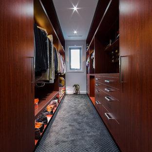Esempio di una cabina armadio per uomo moderna di medie dimensioni con ante in legno scuro, moquette, ante lisce e pavimento blu