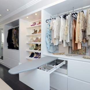 シドニーの広い女性用コンテンポラリースタイルのおしゃれな収納・クローゼット (フラットパネル扉のキャビネット、白いキャビネット、塗装フローリング、黒い床) の写真