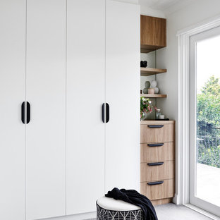This is an example of a contemporary walk-in wardrobe in Sydney with flat-panel cabinets, white cabinets, carpet and grey floor.