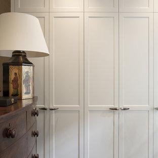 Diseño de armario vestidor de hombre, tradicional, de tamaño medio, con armarios estilo shaker, puertas de armario blancas y moqueta