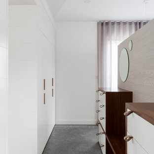 This is an example of a contemporary gender-neutral dressing room in Sydney with flat-panel cabinets, white cabinets, concrete floors and grey floor.
