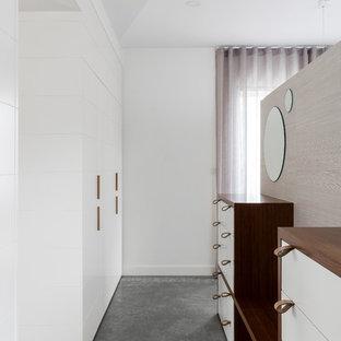 Foto di uno spazio per vestirsi unisex minimal con ante lisce, ante bianche, pavimento in cemento e pavimento grigio