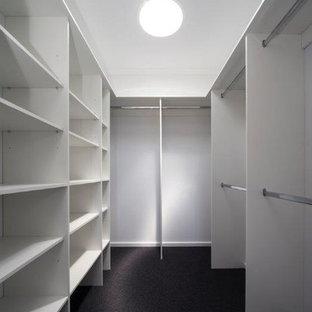 キャンベラの中サイズの男女兼用コンテンポラリースタイルのおしゃれなウォークインクローゼット (オープンシェルフ、白いキャビネット、カーペット敷き、黒い床) の写真