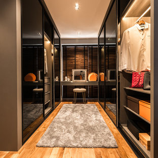 Medium sized contemporary dressing room for women in Singapore with flat-panel cabinets and medium hardwood flooring.