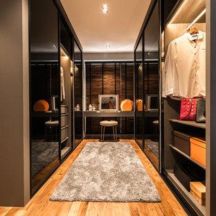 Modelo de vestidor de mujer, actual, de tamaño medio, con armarios con paneles lisos y suelo de madera en tonos medios