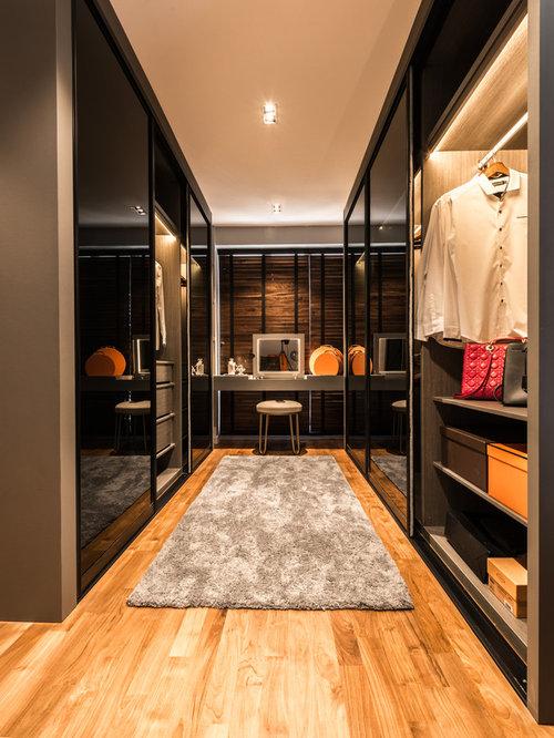 Mittelgroßes Modernes Ankleidezimmer Mit Ankleidebereich, Flächenbündigen  Schrankfronten Und Braunem Holzboden In Singapur