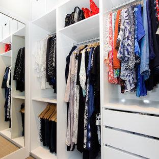 Foto på ett litet funkis walk-in-closet för könsneutrala, med släta luckor, vita skåp, heltäckningsmatta och beiget golv