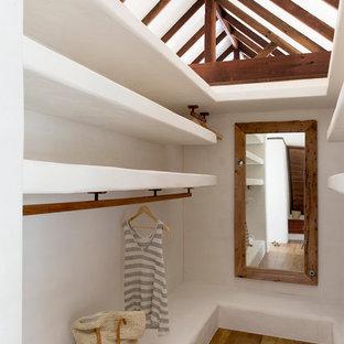 Ispirazione per una cabina armadio unisex tropicale con pavimento in legno massello medio e pavimento marrone
