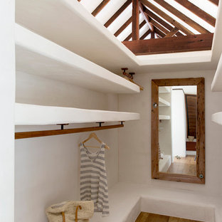 Foto de armario vestidor exótico con armarios abiertos, suelo de madera en tonos medios y suelo marrón