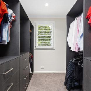 Cette image montre un dressing room avec un placard sans porte, des portes de placard en bois sombre, moquette et un sol rose.