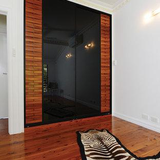 Idee per un armadio o armadio a muro unisex tropicale con ante di vetro, ante in legno scuro e pavimento in legno massello medio