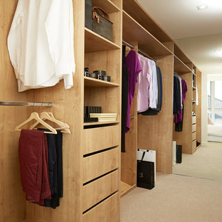 Inspiration for a contemporary gender-neutral walk-in wardrobe in Perth with flat-panel cabinets, light wood cabinets, carpet and beige floor.