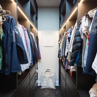 Aménagement d'un dressing moderne de taille moyenne et neutre avec un placard sans porte, des portes de placard en bois sombre, moquette et un sol noir.