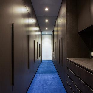 Cette photo montre un dressing moderne avec des portes de placard en bois sombre, moquette et un sol bleu.