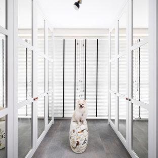 Modelo de armario vestidor de mujer, bohemio, con armarios con paneles empotrados, puertas de armario blancas y suelo gris