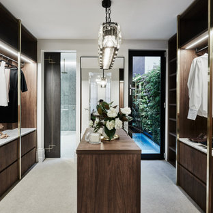Contemporary gender-neutral dressing room in Melbourne with dark wood cabinets and grey floor.