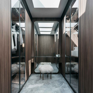 Photo of a contemporary walk-in wardrobe in Sydney with porcelain floors, grey floor, glass-front cabinets and dark wood cabinets.