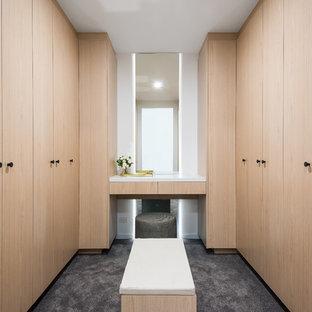 Foto de armario vestidor unisex, actual, grande, con puertas de armario de madera clara y moqueta