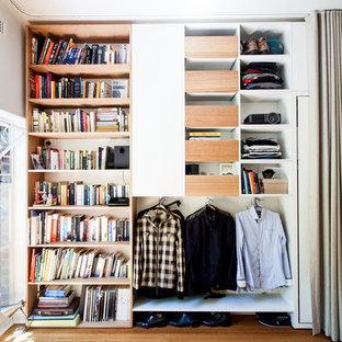 Modelo de armario de hombre, actual, pequeño, con armarios abiertos, puertas de armario de madera oscura y suelo de madera en tonos medios