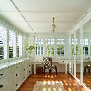 На фото: гардеробная комната унисекс в стиле современная классика с фасадами в стиле шейкер, белыми фасадами, паркетным полом среднего тона и оранжевым полом с