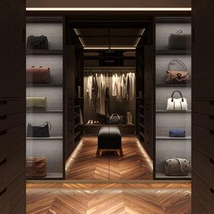 Foto de armario vestidor unisex, moderno, de tamaño medio, con armarios abiertos, puertas de armario de madera en tonos medios y suelo de madera oscura