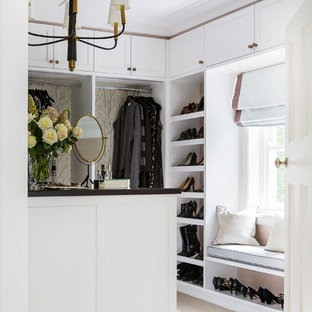 This is an example of a traditional women's walk-in wardrobe in Sydney with shaker cabinets, white cabinets, carpet and beige floor.